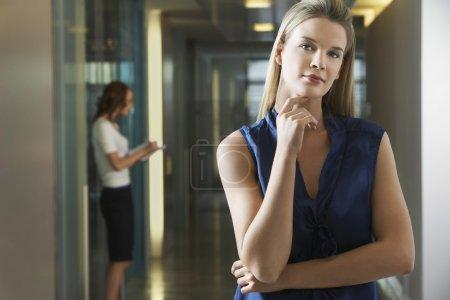 Woman standing in office corridor