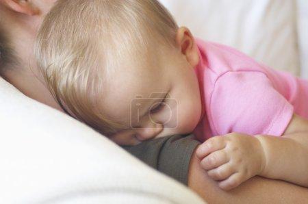 Baby sleeping on mother shoulder