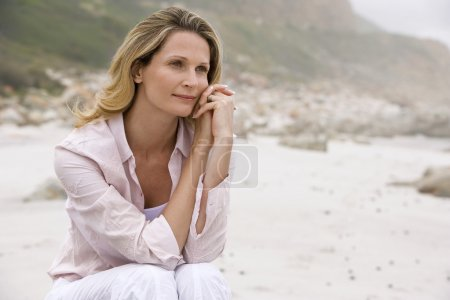 Photo for Pensive woman sitting on beach - Royalty Free Image