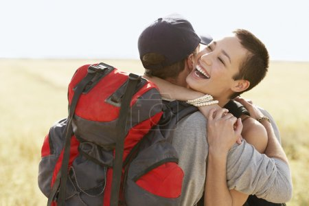 Couple of hikers hugging in field