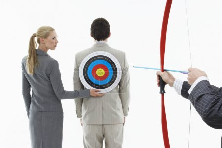 Business woman holding target to man's back