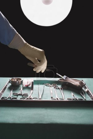 Surgeon hand reaching for medical equipment
