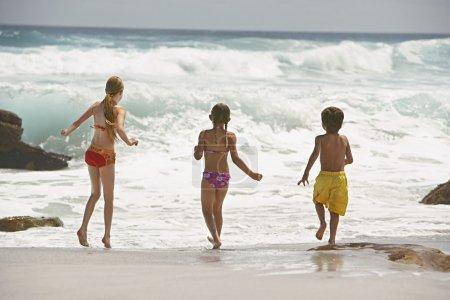 Photo pour Enfants gais courant dans l'eau, vue arrière - image libre de droit
