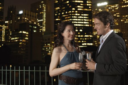 Photo for Elegant happy young couple with champagne flutes against cityscape at night - Royalty Free Image