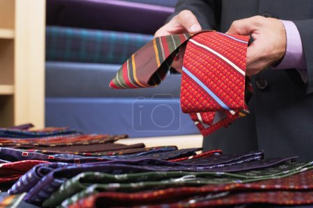 Businessman selecting ties in clothes store