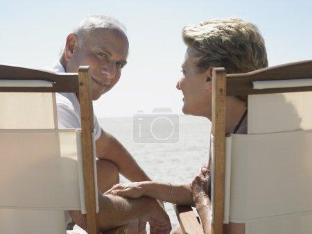Photo pour Senior homme avec la femme assise sur les chaises longues à la plage - image libre de droit
