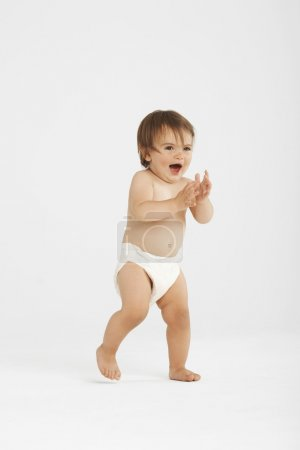 Photo pour Bébé excité faisant ses premiers pas en studio blanc - image libre de droit