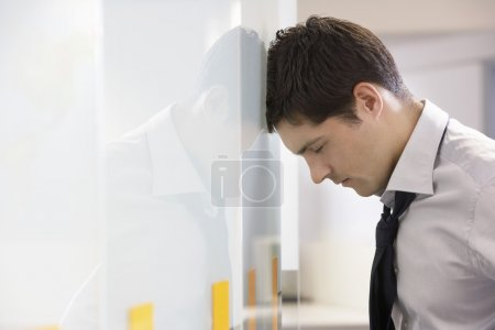 Unhappy Businessman resting head against wall