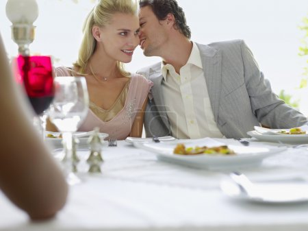 Photo for Couple Whispering at Dinner - Royalty Free Image
