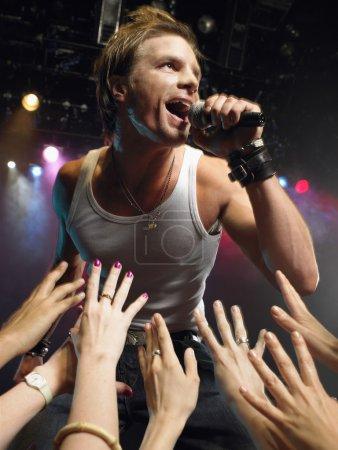 Photo pour Vue en angle bas de rock star masculine chantant sur scène avec des fans adorant atteindre leurs mains vers lui - image libre de droit