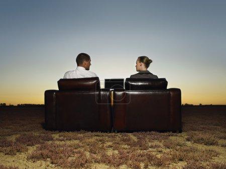 Photo pour Deux hommes d'affaires dans des fauteuils en plaine ouverte au coucher du soleil - image libre de droit