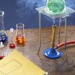 Bunsen burner heating flask with science equipment...