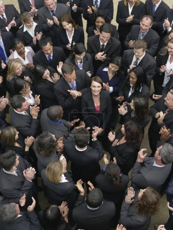 Photo for Large group of business people clapping surrounding woman looking up elevated view - Royalty Free Image