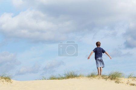 Photo pour Jeune garçon debout sur une dune de sable dans le vent avec les bras tendus vue arrière - image libre de droit