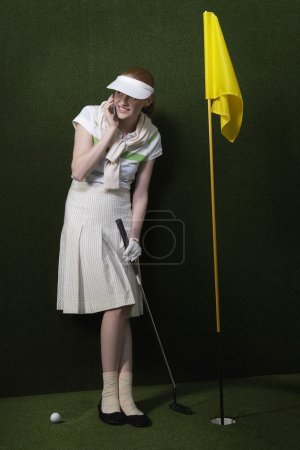 Photo for Golfer Using Cell Phone in Indoor Putting Green - Royalty Free Image