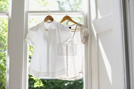 Photo for White blouses on Hangers in domestic window - Royalty Free Image