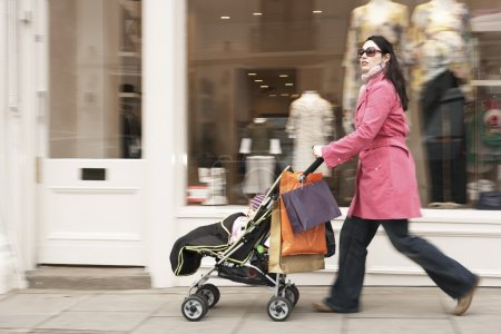 Mother pushing stroller by shop