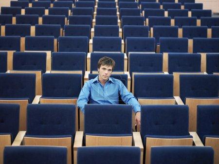 empresario sentado en auditorio