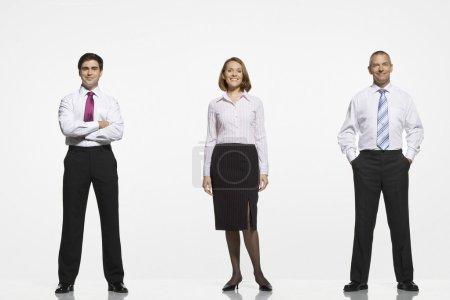 Photo pour Businesspeople, debout à côté bras traversés par côté dans les poches - image libre de droit