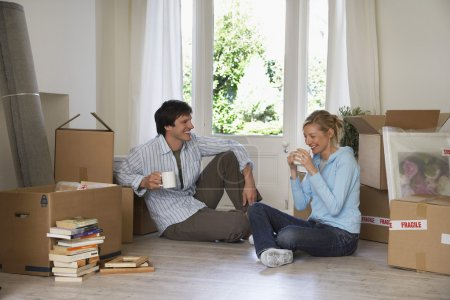 Couple taking a break among moving boxes