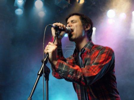 Photo pour Jeune homme chantant dans le microphone sur scène au Concert vue basse - image libre de droit