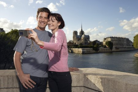 Photo for Paris France Couple taking a photo of themselves in front of Notre Dame Cathedral - Royalty Free Image