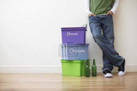 Photo for Low section view of young man leaning against wall next to small pile of recyling containers - Royalty Free Image