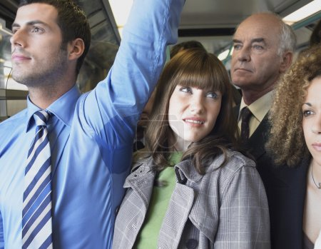 Photo for Female Commuter Standing by Man's Wet Armpit on Train - Royalty Free Image