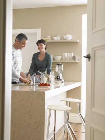 man washing utensils with woman in kitchen