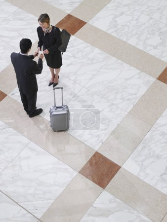 Business man presenting business card to business woman