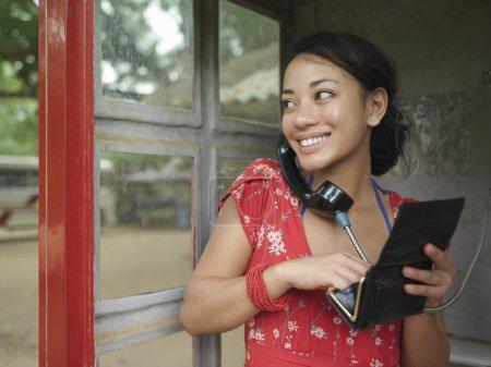 Woman using public phone