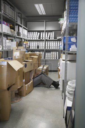 Woman using laptop in storage room