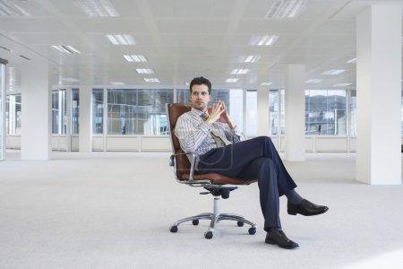 Office worker sitting in swivel chair in empty off...