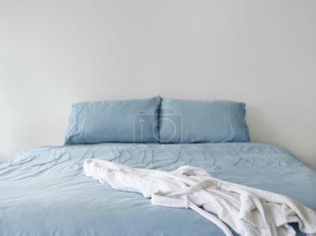 Bathrobe on unmade empty bed