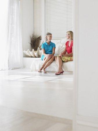 Women talking sitting on sofa