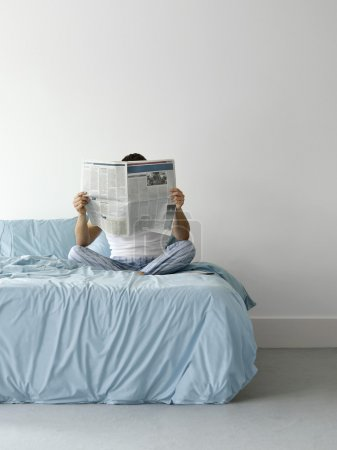 Man on bed reading newspaper