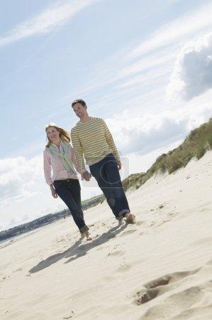 Photo pour Couple tenant la main marchant sur la plage - image libre de droit
