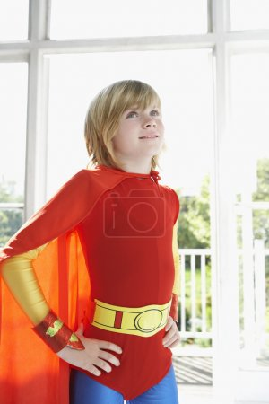 Boy in superhero costume with hands on hip