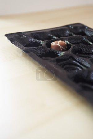 Photo pour Boîte de chocolat avec une seule truffe restant en gros plan - image libre de droit