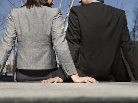 Photo pour Homme d'affaires et femme assis sur le mur en plein air vue de l'arrière - image libre de droit