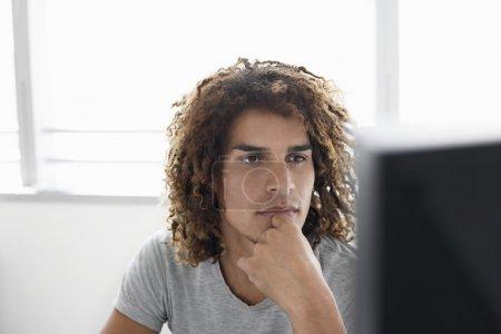 Photo pour Jeune homme bi racial à l'aide d'ordinateur tout en étant assis au bureau - image libre de droit