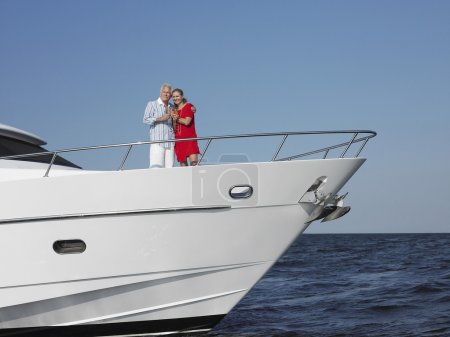Couple standing in bow of yacht