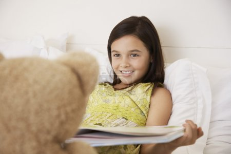 Girl reading book to teddy bear