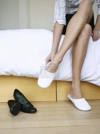 female legs putting slippers on