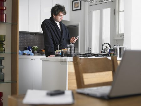 Man messaging with phone in kitchen