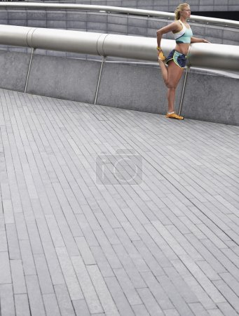female athlete stretching on footbridge
