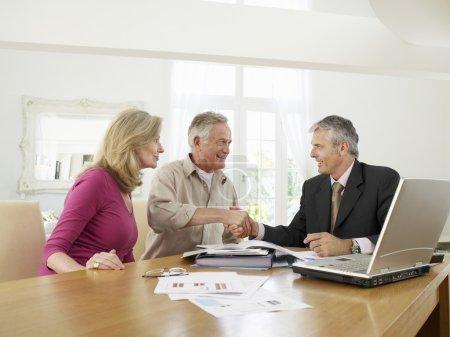 Photo pour Couple âgé assis à la table avec un conseiller financier - image libre de droit