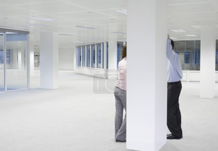 Photo for Two office workers talking behind column in empty office space - Royalty Free Image