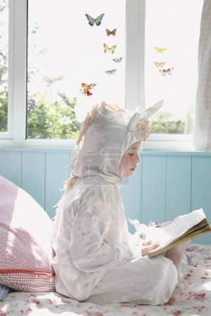 Photo for Little girl in unicorn costume  sitting on bed and reading book, side view - Royalty Free Image