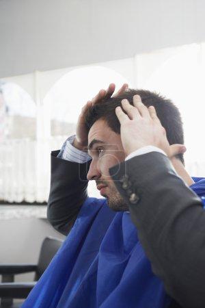 Business man checking cut hair